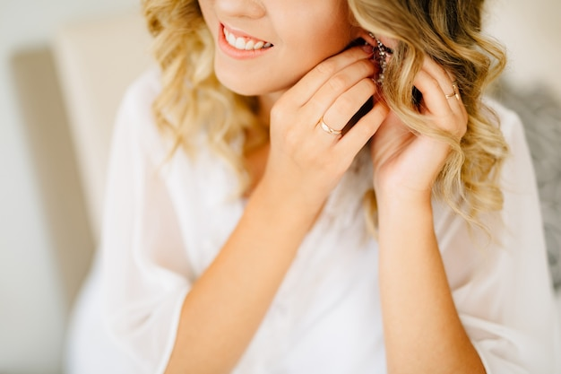 白いペニョワールを身に着けている花嫁は、結婚式の準備をしながらイヤリングと笑顔を着ます