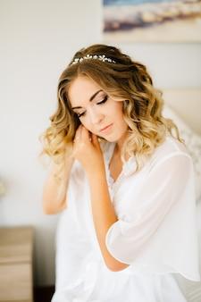 白いペニョワールを身に着けている花嫁は、結婚式の準備中にイヤリングを着用します
