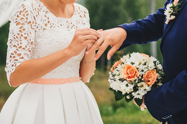 Bride wears a ring on groom's finger at wedding