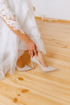 The bride wears shoes on a wedding morning