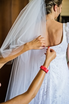 The bride wears a white wedding dress, hands tied corset