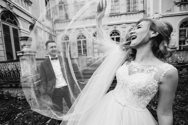 Bride in wedding dress smiling and holding a bridal veil