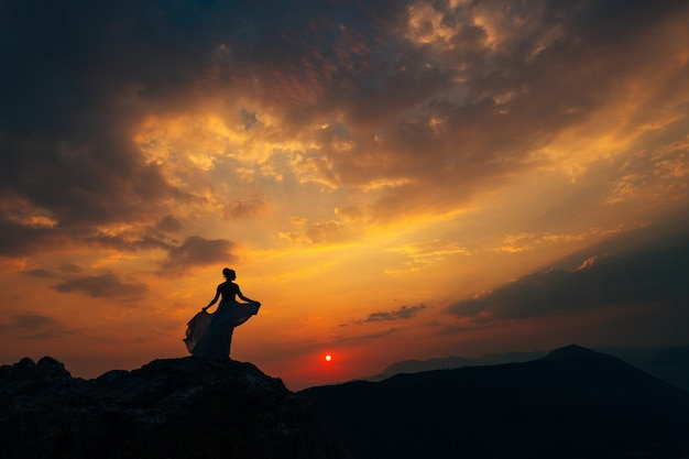 A bride in a wedding dress whirls on the top of mount lovcen at sunset