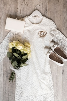 Bride wedding dress with shoes clutch; hairbands and rose bouquet tied with white ribbon on wooden background