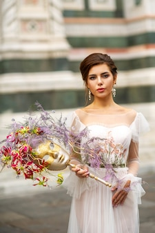 A bride in a wedding dress with a venetian mask in her hands in florence.italy.