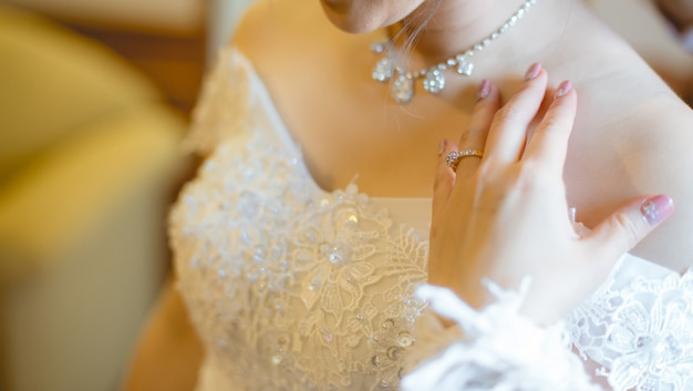 The bride in a white dress and her hand with a wedding ring wearing on her finger.