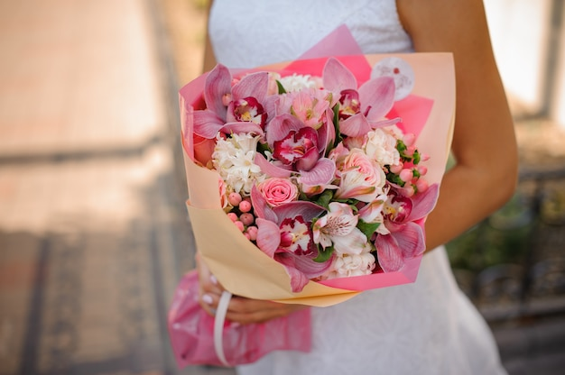 Bride in white dress holding a beautiful bouquet of flowers