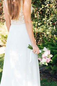Bride in white dress holding flower bouquet in hand