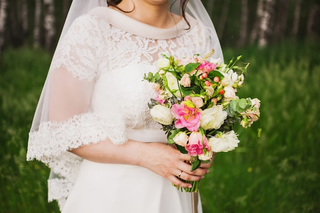 The bride in a white dress holding a wedding bouquet of white, red and pink colors. white and pink roses. morning bride