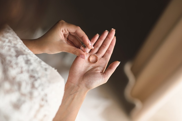 Bride in a white dress holds gold wedding rings in her hands