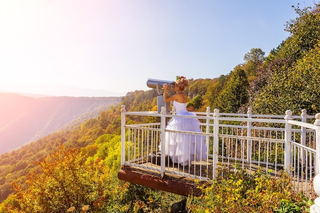 A bride in a white dress on the observation deck looks through stationary binoculars binoscope
