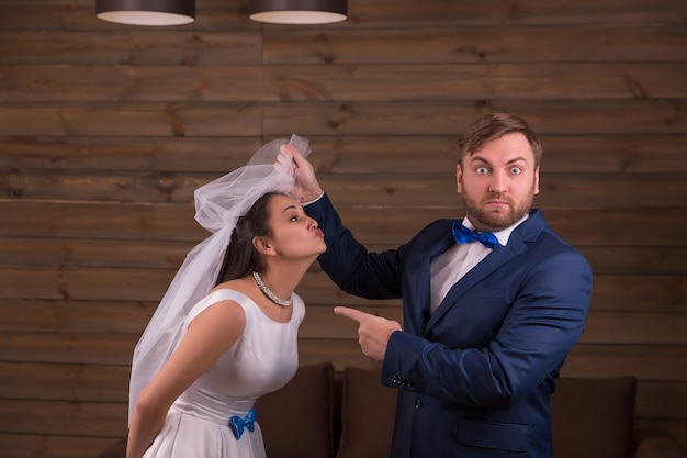 Bride in white dress and veil against surprised groom in suit and bow tie on wooden room