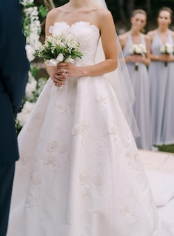 Bride in a white dress with a bouquet in her hands stands next to the groom on the lawn