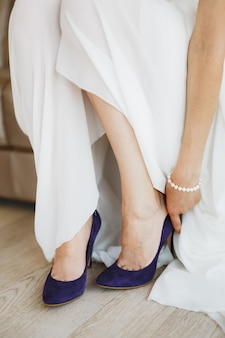 Bride in a white dress with a pearl bracelet on her arm wears blue highheeled shoes on her feet