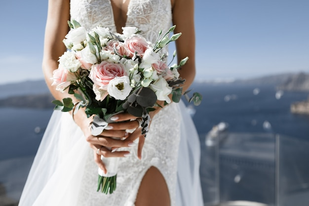 Bride in a white dress with a slit holds bouquet on background of sea and sky