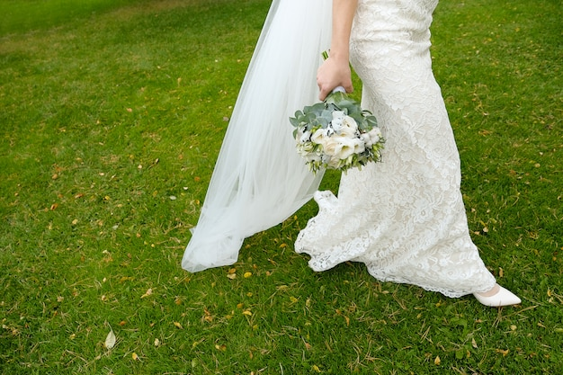 A bride in a white elegant wedding dress holds a wedding bouquet in her hands. selective focus
