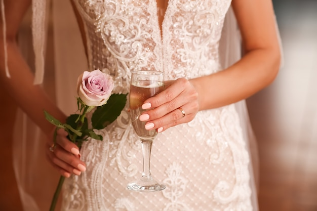 Bride in white lace dress holding a glass of champagne and a rose