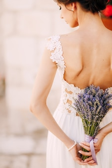 Bride in a white lace dress stands with her head bowed and holds a lavender bouquet tied with a