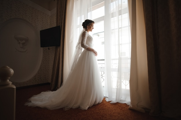 Bride in a white lace dress with a plume stands against the window