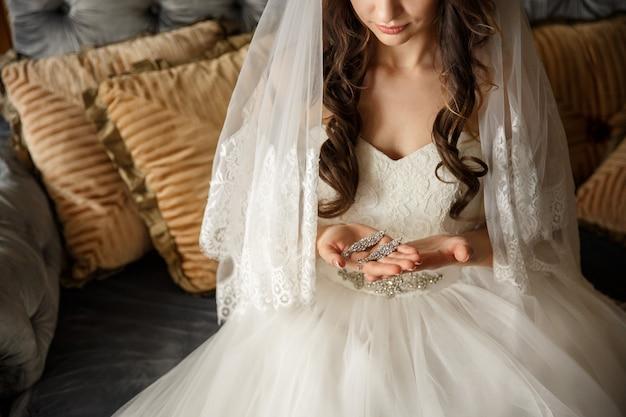 Bride in white wedding dress holding bridal jewelry. wedding concept