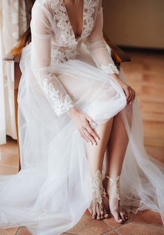 Bride in white wedding dress opened barefoot while sitting on a chair