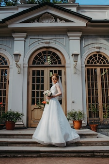 The bride in a white wedding dress stands at the castle.