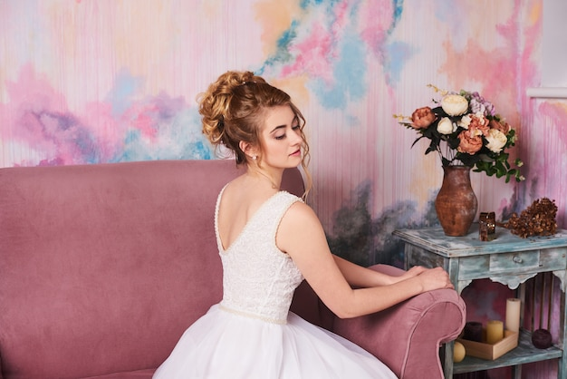 Bride in white wedding dress without veil sit on pink sofa at home