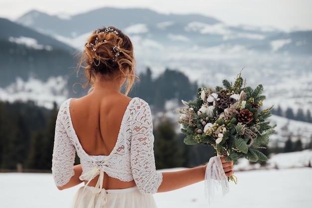 Невеста зимой в белом свадебном платье, держа в руках букет цветов
