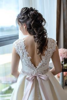 白いドレスを着た長い髪の美しい髪型の花嫁が立ち上がる