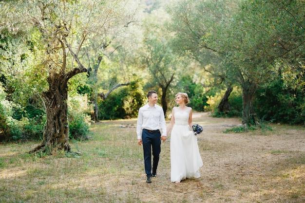 青い花の花束を持った花嫁と花婿がオリーブの木立の中を並んで歩き、抱きしめます