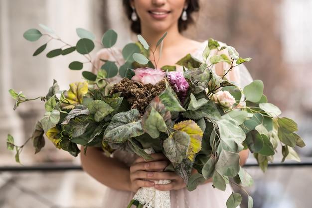 大都会の通りに囲まれたバルコニーに花束を持った花嫁