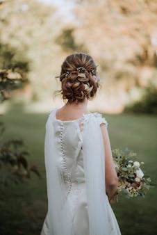 花の花束を保持しているウェディングドレスを着てブライダルヘアスタイルの花嫁