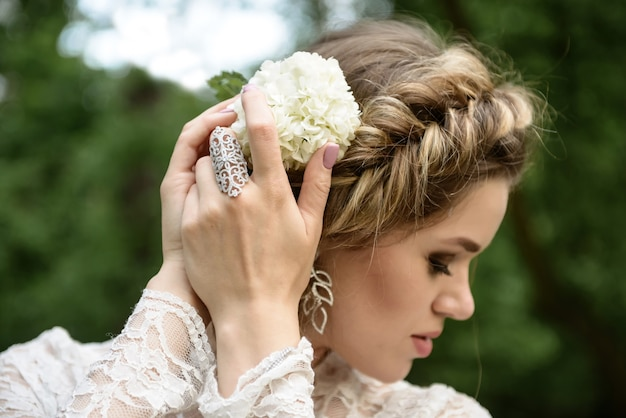 Bride with a beautiful braid on her head straightens a flower portrait