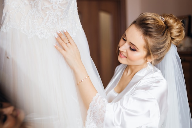 Bride with beautiful hairstyle and makeup in white bathrobe looks at wedding dress.