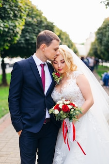 Bride with beautiful makeup closed her eyes leaned against the groom and holds a wedding bouquet