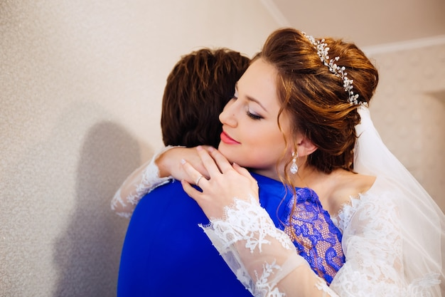 Bride with beautiful makeup and elegant hairstyle embraces her mother against the background of the wall