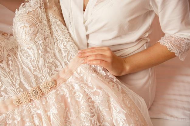 Bride with beautiful manicure holding wedding dress. wedding preparation of bride.