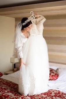 Bride with beautiful manicure holding wedding dress.