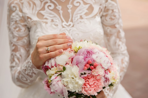 Bride with beautiful wedding manicure holding wedding bouquet