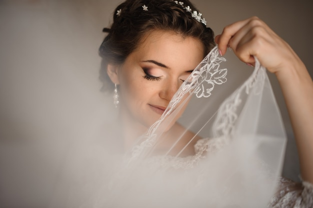 Bride with blue eyes covers her lips with a veil