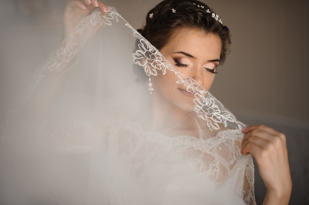 Bride with blue eyes and gentle make-up covers her lips with a veil