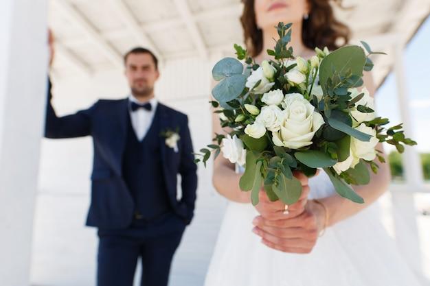 バックグラウンドで花束と新郎と花嫁は、屋外で結婚式のカップルをクローズアップ