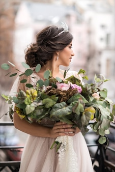 Bride with a bouquet of flowers on the balcony among the streets of the big city