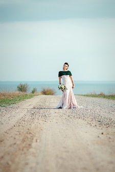 Bride with a bouquet of flowers in an ivory dress and a knitted shawl on the road stretching into the distance