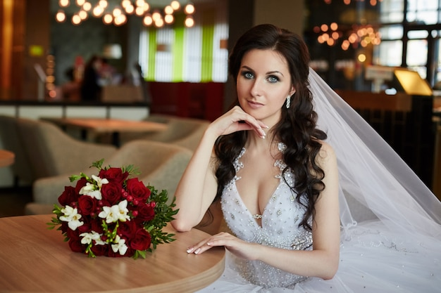 Bride with a bouquet of flowers sitting at table