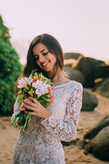 Bride with bouquet in hands is standing on beach and smiling