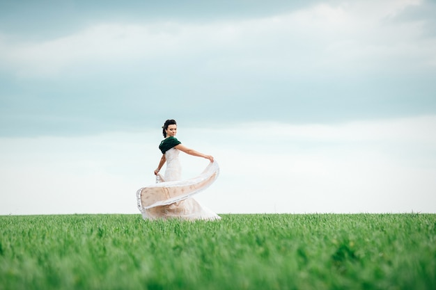 Bride with a bouquet in an ivory dress and a knitted shawl on a green field