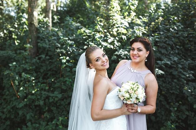 Bride with bridesmaid posing in garden