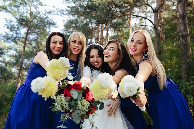 Bride with bridesmaids holding bouquets posing