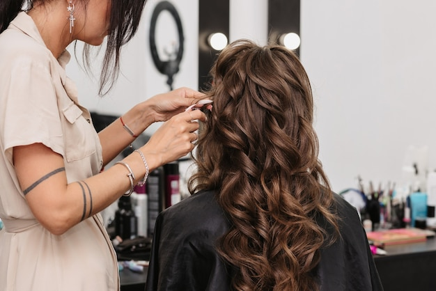 Bride with brown curly long hair in a beauty salon